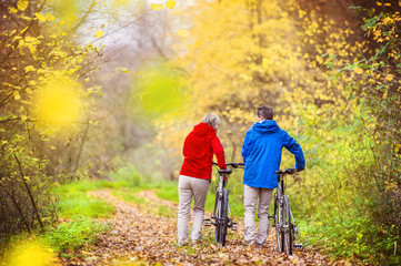 Active seniors walking with bike