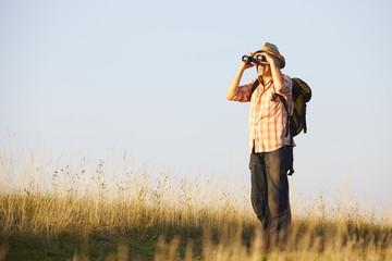 Wanderer mit Fernglas auf Wiese