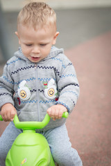 Baby Boy Riding a Plastic Scooter