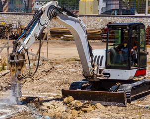 Excavator with demolition hammer in a construction site