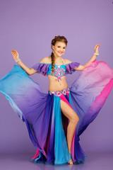 Beautiful belly dancer wearing a purple costume
