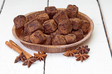 Chocolate truffles and cinnamon on wooden background