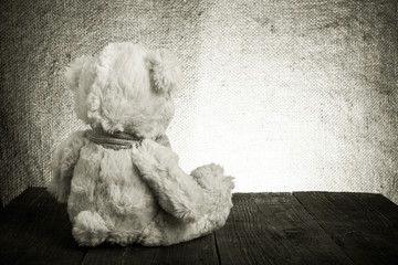 Teddy bear is sitting on the old wooden table. Toned
