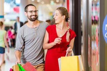 Paar an Schaufenster vor Laden in Einkaufzentrum