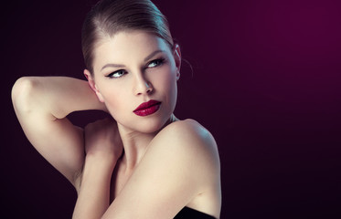 Young elegant woman with retro makeup over dark background