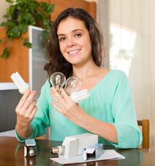 Woman with armful of lightbulbs