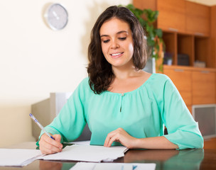 Smiling brunette woman reading document
