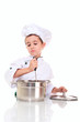 Little boy chef with ladle stiring in the pot