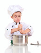 Little boy chef with ladle stiring in the pot by both hands