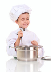 Little happy boy chef with ladle stiring in the pot