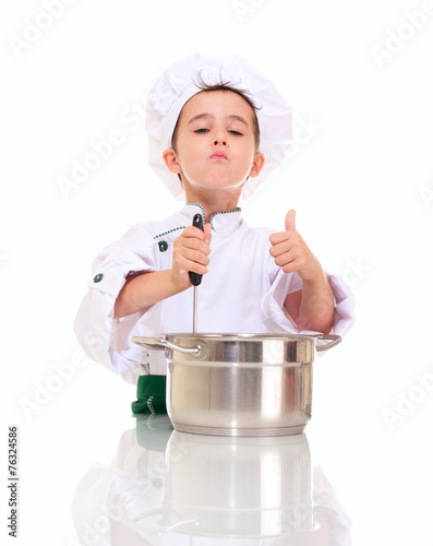 Little satisfied boy chef with ladle stirring in the pot