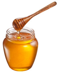 Honey flowing into glass jar. File contains clipping paths.