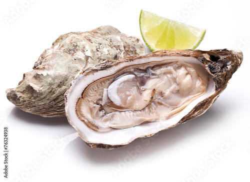 Raw oyster and lemon on a whte background. - 76324938
