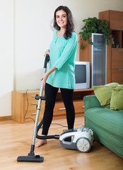 Brunette woman cleaning living room