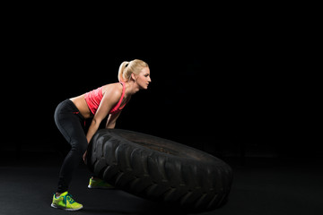 Muscular woman use big tire as part of Crossfit Training
