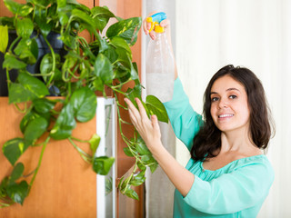 housewife with spray houseplant