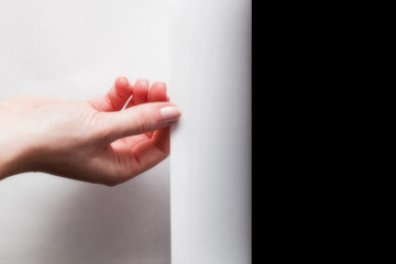 Hand pulling edge of paper to uncover, reveal something