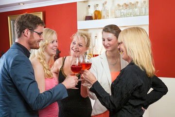 Group of friends celebrating with rose wine.