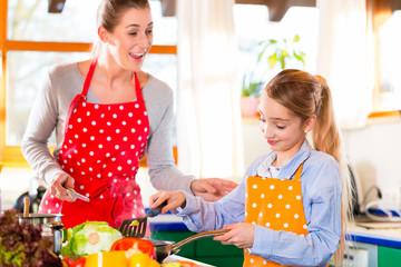 Mutter bringt Tochter das Kochen bei