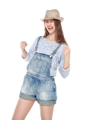 Young fashion girl in jeans overalls with yes gesture isolated