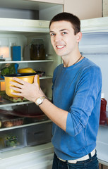 man with saucepan  near refrigerator
