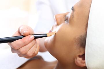 Kosmetyczka nakłada  maseczkę nawilżającą na twarz kobiety.