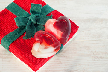 Gift - Valentine heart shaped two soap on red towel.