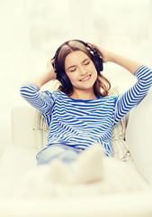 smiling young girl in headphones at home