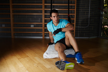 Athlete seated on fitness mat having a rest after workout