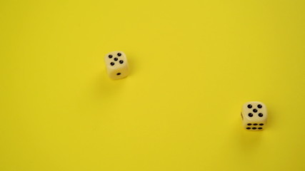 Rolling Dice on Yellow Background as Gambling Concept