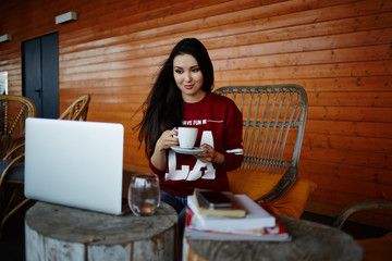 Young woman drink coffee using computer laptop in cafe