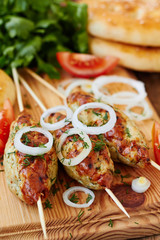 Minced meat kebab on skewers with vegetables and flat bread