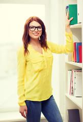 smiling female student in eyeglasses choosing book
