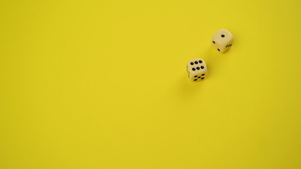 Rolling Dice on Yellow Background as Gambling and Probability co