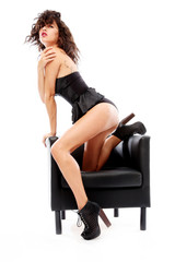 Sensual girl with black underwear sitting on the armchair