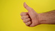 Thumbs Up For Like, male hand endorsing over yellow background,