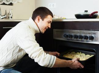 Smiling guy roasting meat