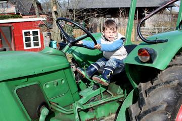 Kind am Steuer eines Traktors