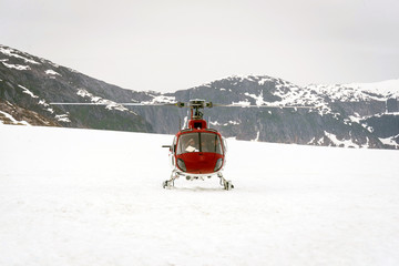 Helicopter landing on glacier in between snowy mountains