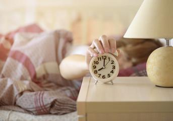 girl turns off the alarm clock