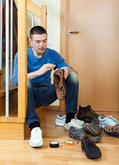 Young  man  cleaning footwear