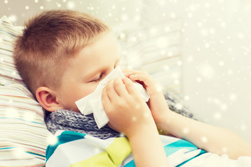 ill boy blowing nose with tissue at home