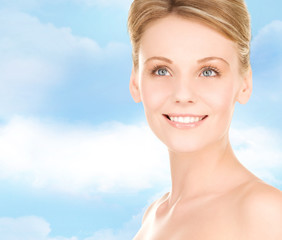 close up of smiling woman over blue sky background