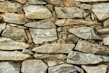 Cracked real stone wall surface with cement.