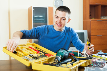Smiling man organizing tools in toolbox