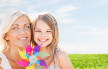 happy mother and little girl with pinwheel toy