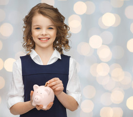 smiling girl putting coin into piggy bank