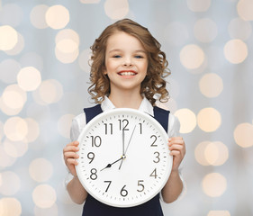 smiling girl holding big clock
