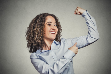 Fit young healthy woman flexing muscles showing her strength