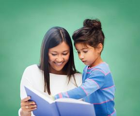 happy teacher and little schoolgirl reading book